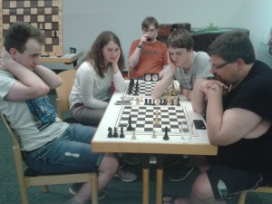 Sieben Leute (zwei nicht auf dem Foto) sitzen um eine Schachbrett herum, auf dem nur zwei Könige stehen. Was sich im ersten Moment ziemlich sinnlos anhört, ist in Wirklichkeit eine ziemlich schwierige Retroschachaufgabe.
